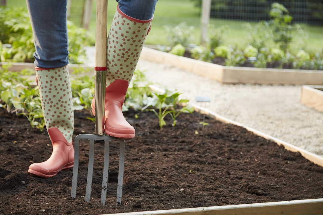Person digging a hole with a garden fork in a raised bed.