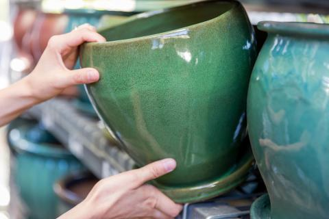 Man grabbing a ceramic green pot of a store shelf.