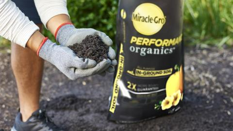 A person in gardening gloves holds a scoop of Miracle-Gro Performance Organics soil in his hands.