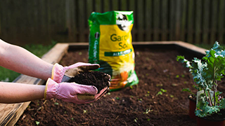 Person putting soil into a raised bed garden.