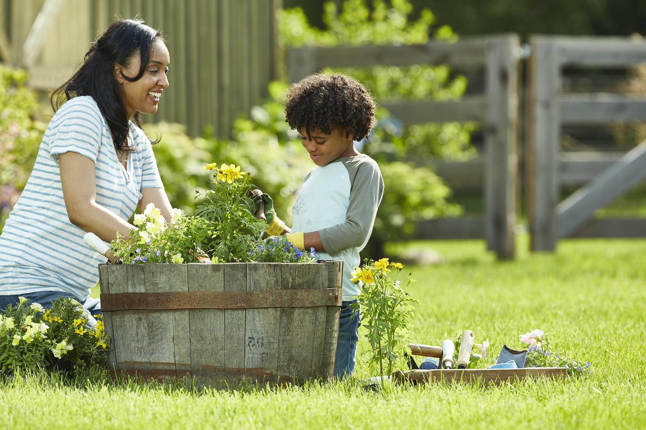 A woman and child plant a mix of flowers in an upcycled, half-whiskey barrel as part of their container garden in the yard.