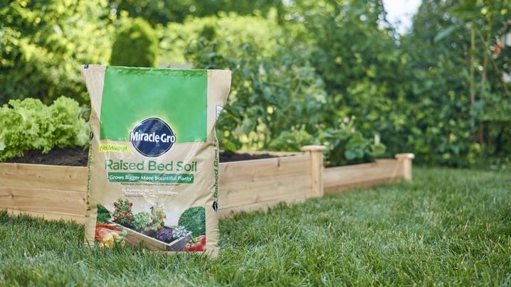 Bag of Miracle-Gro® Raised Bed Soil near a raised bed.