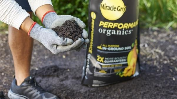 hands holding Miracle-Gro® Performance Organics™ All Purpose In-Ground Soil