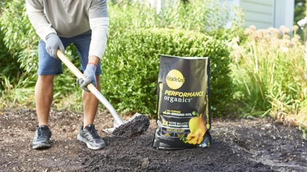 man shoveling next to bag of miracle-gro performance in-ground soil