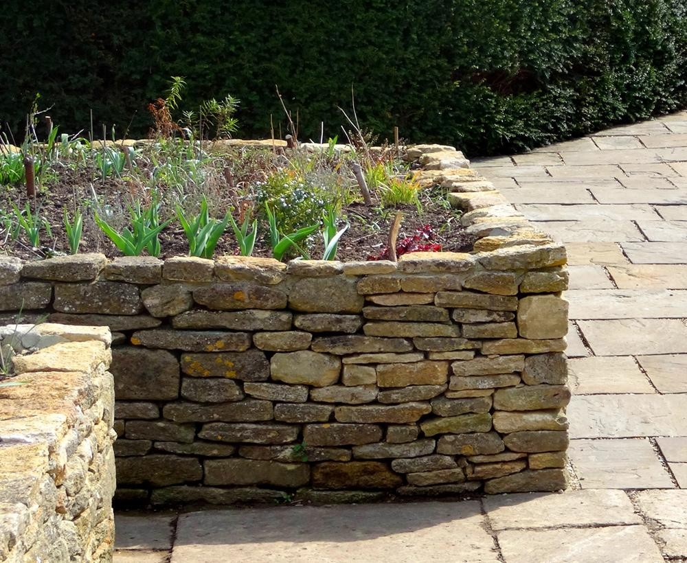A raised bed garden made from dry-stone walls is situated on a patio of flagstone pavers.