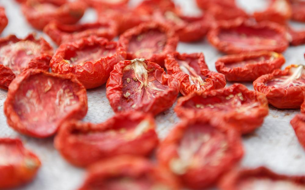 Dried tomatoes placed on a woven mat