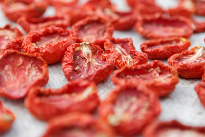Red tomatoes drying on a pan.