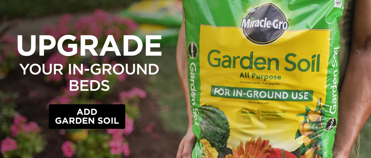 A person holds a bag of Miracle-Gro® All Purpose Garden Soil.