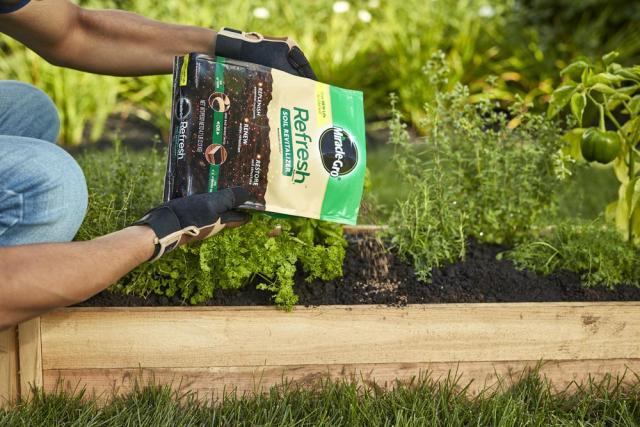 Pouring Miracle-Gro® Refresh 1™ Soil Revitalizer