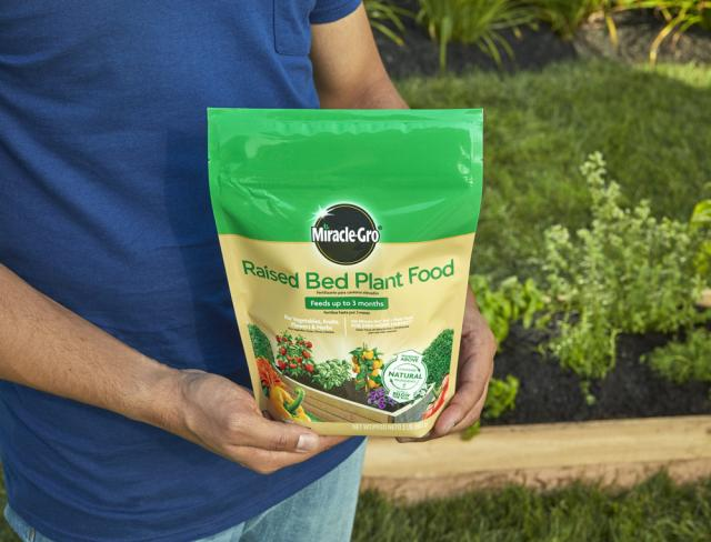 holding Miracle-Gro® Raised Bed Plant Food