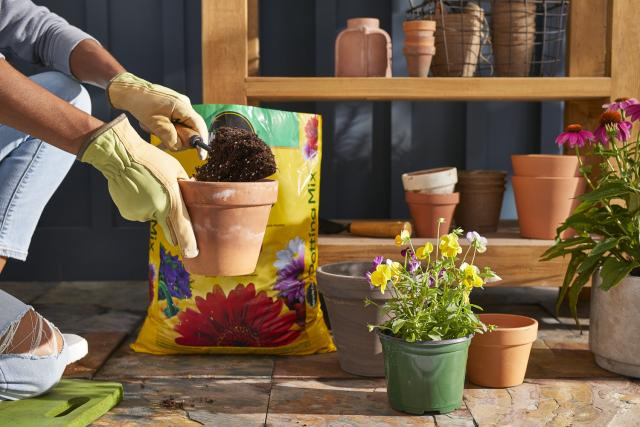 Miracle-Gro® Potting Mix being scooped into pot