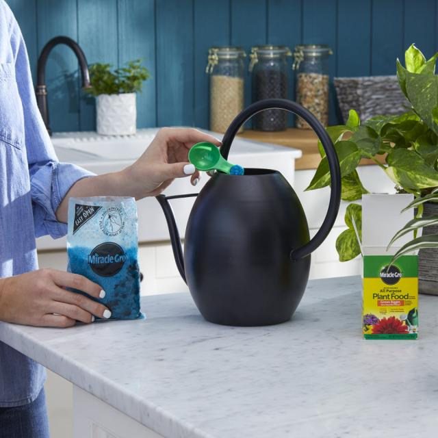 User mixing product into watering can