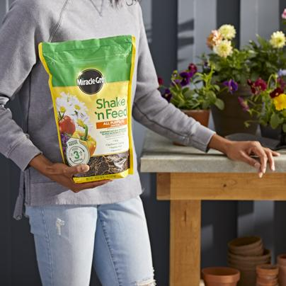 Person holding Miracle-Gro® Shake 'n Feed® All Purpose Plant Food.